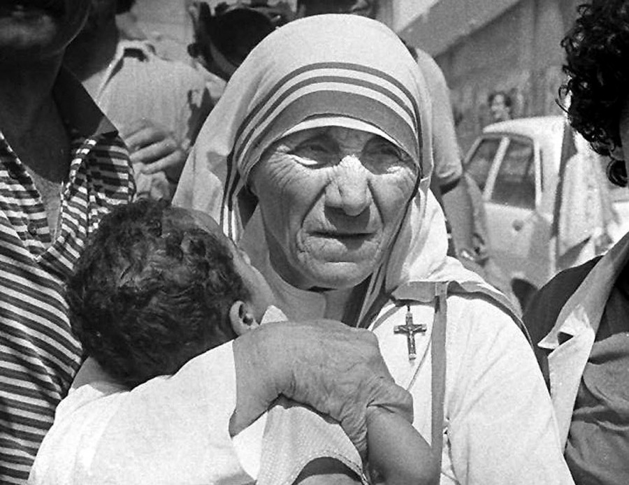Madre teresa de calcuta ayudando a un niño
